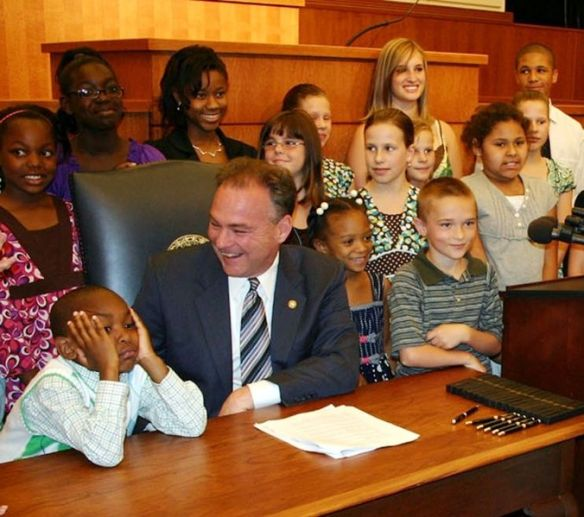 A politician surrounded by many childrens. Intellectual equals.