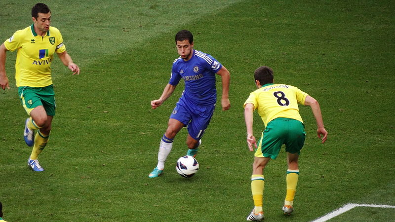 Eden Hazard taking on Norwich defenders, while storing nuts in his cheeks.